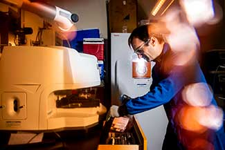 Aron Stubbins, associate professor of marine & environmental sciences and civil & environmental engineering, inspects microplastics from the open ocean.