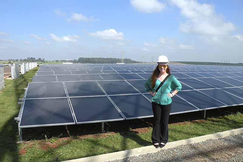 student in hard hat with rows of solar panels in background