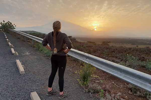 girl in jogging clothes with hands on him on road looking out at sunset